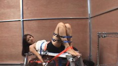 Innocent young brunette is strapped down and immobile in a bondage scene