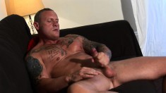 Hot muscled stud lies on the couch and takes his long dick to orgasm