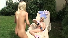 Two platinum blonde babes take care of each other's pussy outside