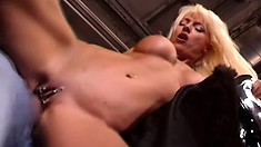 Hot busty blonde is in the garage where she feels the best getting fucked